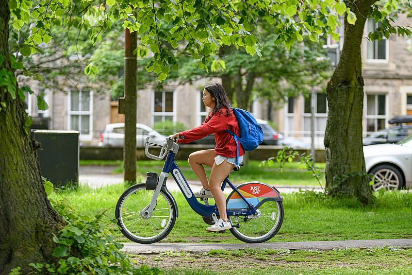 A young woman riding a hire bike through the Meadows in Edinburgh