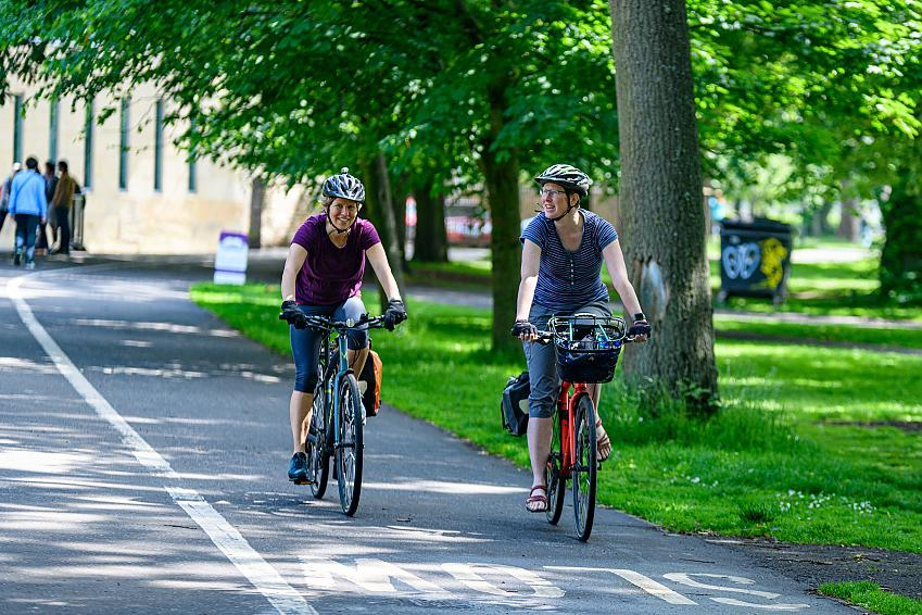 Two women smiling as they cycle through the Meadows in Edinburgh