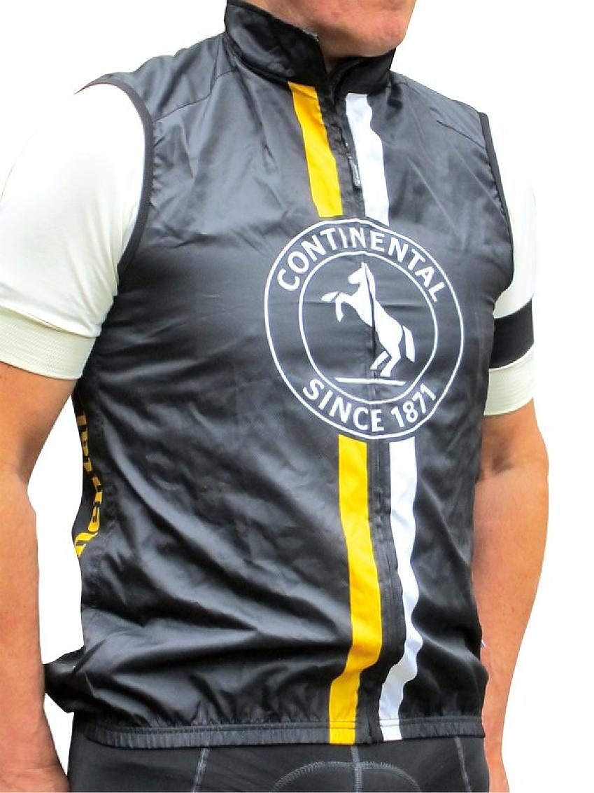 A man wears a black gilet with vertical yellow and white stripes and a dancing horse logo